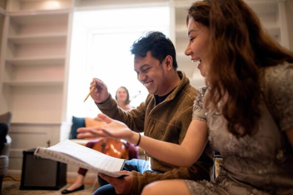 Smiling students review musical score together