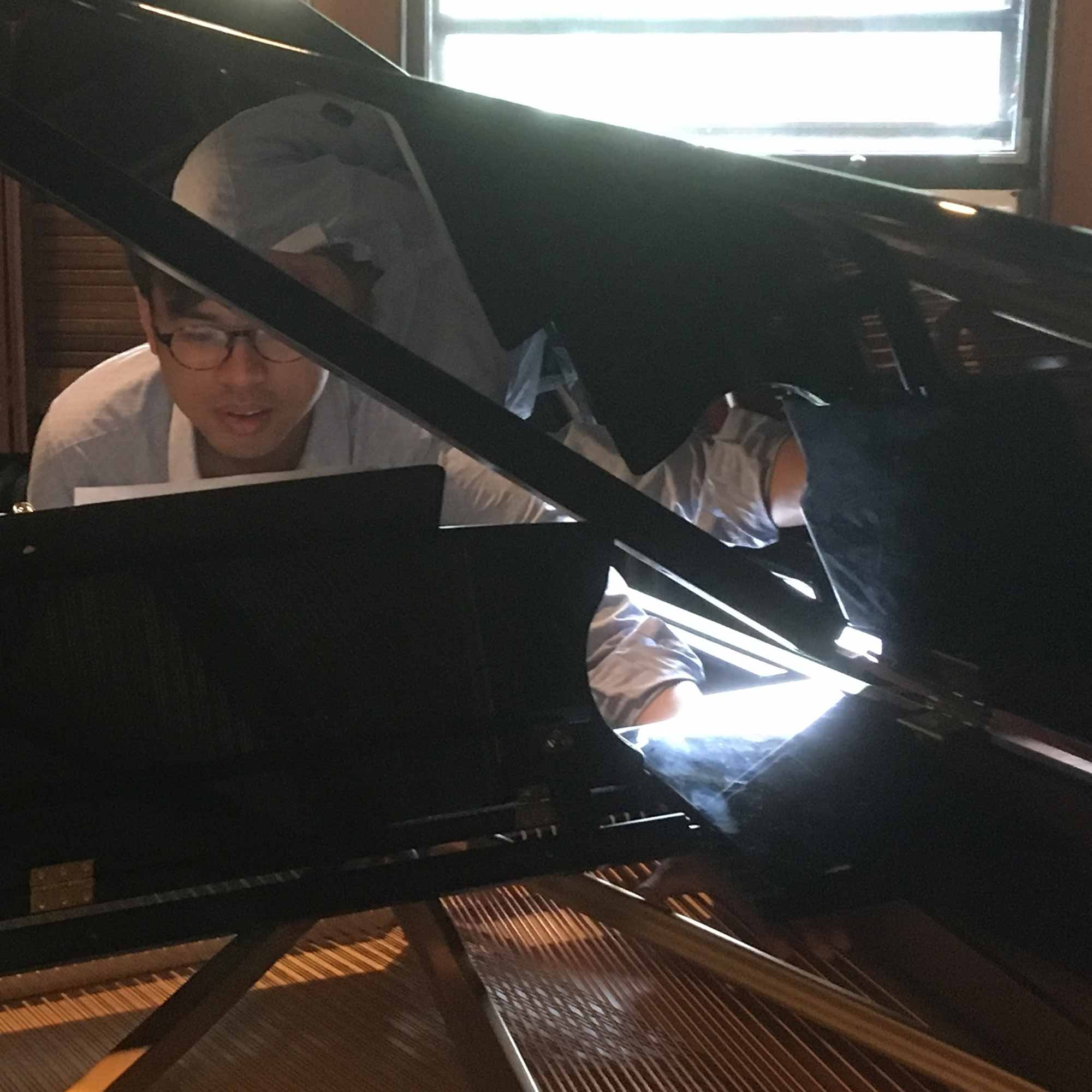 Pianist reaching to play inside piano